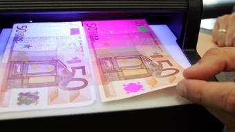 Ein falscher (l.) und ein echter 50-Euro-Schein unter einem UV-Lichtgerät (Symbolbild)