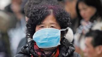 Eine Frau mit Mundschutz in Wuhan.