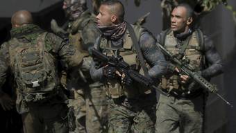 Schwer bewaffnete Militärpolizisten sind im Einsatz. Beim Kampf zwischen Drogenbanden um die Vorherrschaft über einen Favela-Komplex in der brasilianischen Metropole Rio de Janeiro ist es erneut zu heftigen Schießereien gekommen. Foto: O Globo/GDA via ZUMA Wire GDA via ZUMA Wire/dpa