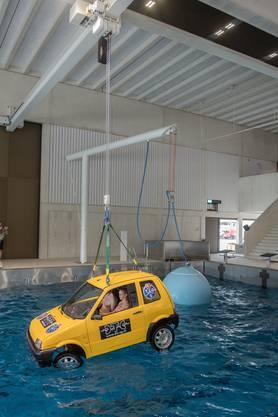 ... und wird sanft zu ins Wasser gelassen. Im Hintergrund ist ein im Wasser liegender Ballon zu sehen, der Wellen erzeut. Er kann elektronisch gesteuert werden.