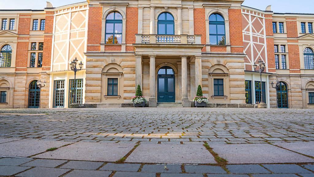 Wolken ziehen über das Bayreuther Festspielhaus. Am 25.07.2021 beginnen die Bayreuther Festspiele. Foto: Nicolas Armer/dpa