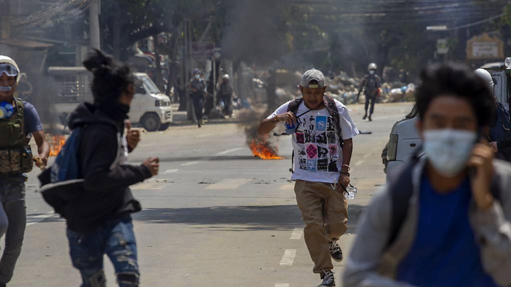 Demonstrantenlaufen vor der Polizeidavon. Seit Beginn der Proteste gegen den Militärputsch in Myanmar sind bei den brutalen Auseinandersetzungen viele zu Tode gekommen. Foto: Uncredited/AP/dpa