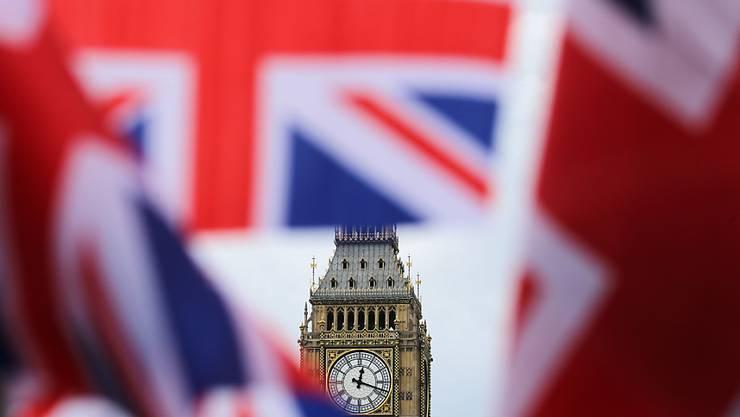ARCHIV - Britische Fahnen wehen vor dem berühmten Uhrturm Big Ben. Das britische Parlament stimmt heute über den Brexit-Handelspakt mit der Europäischen Union ab. Beide Kammern sollen die Vereinbarung innerhalb weniger Stunden abnicken. Foto: Michael Kappeler/dpa