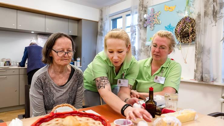 Die Wohnbereichsleiterin Jessica Schmidt (Mitte) zeigt der Bewohnerin Therese Seiler, wie man erkennt, ob ein Ei roh oder gekocht ist. Die Stv. Leiterin Wohnbereich Ursula Leonhardt schaut zu.