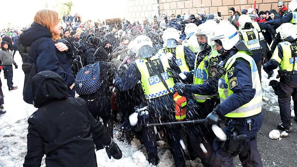 Gegendemonstranten bewerfen Polizisten mit Schneebällen, als diese sie von demonstrierenden Neonazis fernhalten.