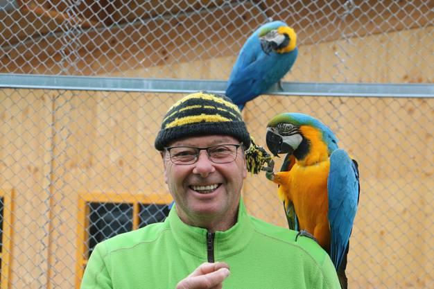 Rolf Lanz posiert mit zwei seiner Vögel im Vogelpark Ambigua.