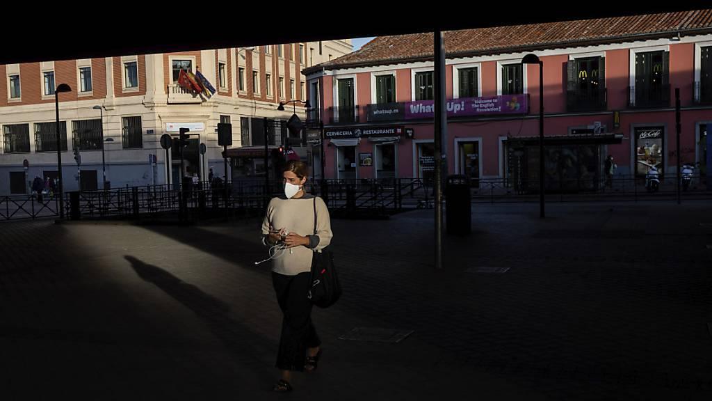 Eine Frau mit Gesichtsmaske auf einem Platz in der spanischen Hauptstadt. Foto: Bernat Armangue/AP/dpa