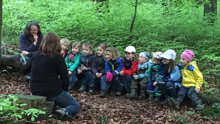 Die Kinder hören auf dem Geschichtenstamm gespannt der Geschichte zu.