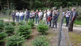Revierförster Beat Bossert (links neben dem Zaunpfosten) und Kreisoberförster Erwin Jansen (ganz rechts) bereicherten den Waldumgang mit vielen Informationen.