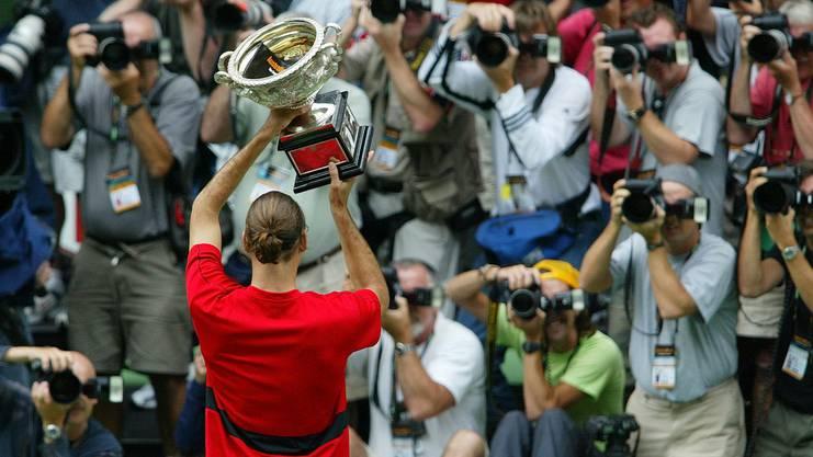 Erster Sieg beim Australian Open gegen Marat Safa und das in glatten drei Sätzen. Stolz präsentiert Federer den Fotografen seinen Pokal.