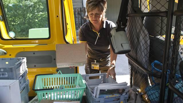 Eine Briefträgerin bringt im Kanton Glarus einem Kunden die Post nach Hause (Archiv)