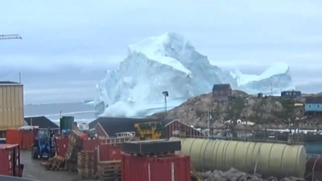 Während wir schwitzen, bedroht dieser Eisberg ein ganzes Dorf