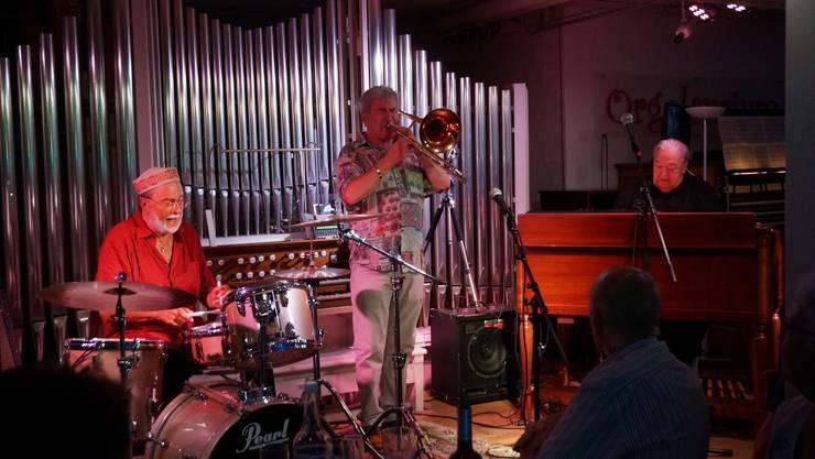Von links: Drummer Brian Wilson Posaunist John Service und Organist George Fleury - sie spielen Jazz-Standard wobei die Posaune gefühlsvoll eine Nachhause-Gehstimmung erzeugt bei der Drums und Orgel noch nicht aufhören wollen.