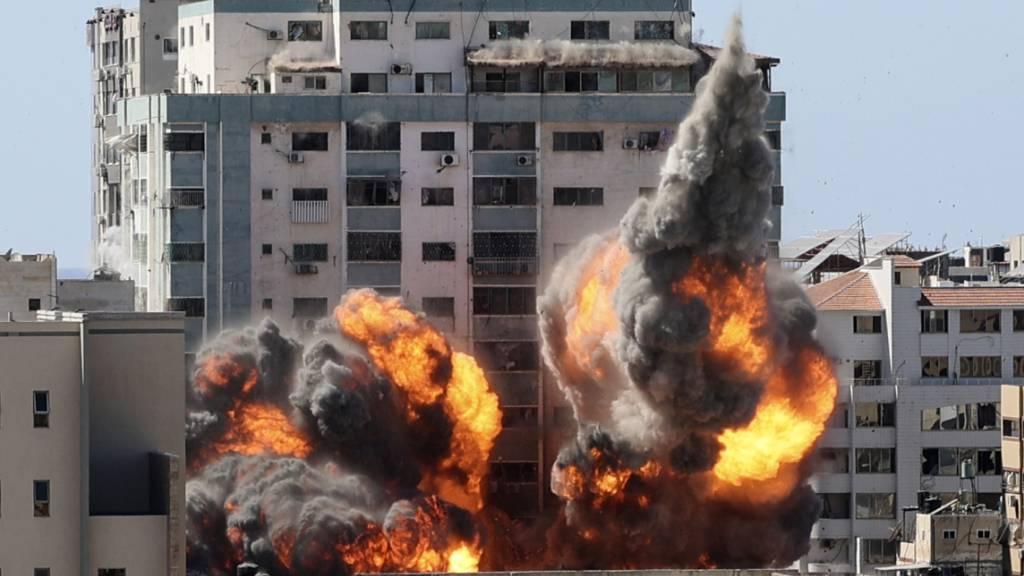 dpatopbilder - Rauch und Feuer steigen aus einem Gebäude nach einem israelischen Luftangriff auf. In dem Gebäude sind verschiedene internationale Medien untergebracht, darunter auch die Associated Press und Al-Dschasira. Foto: Mahmud Hams/POOL AFP/AP/dpa