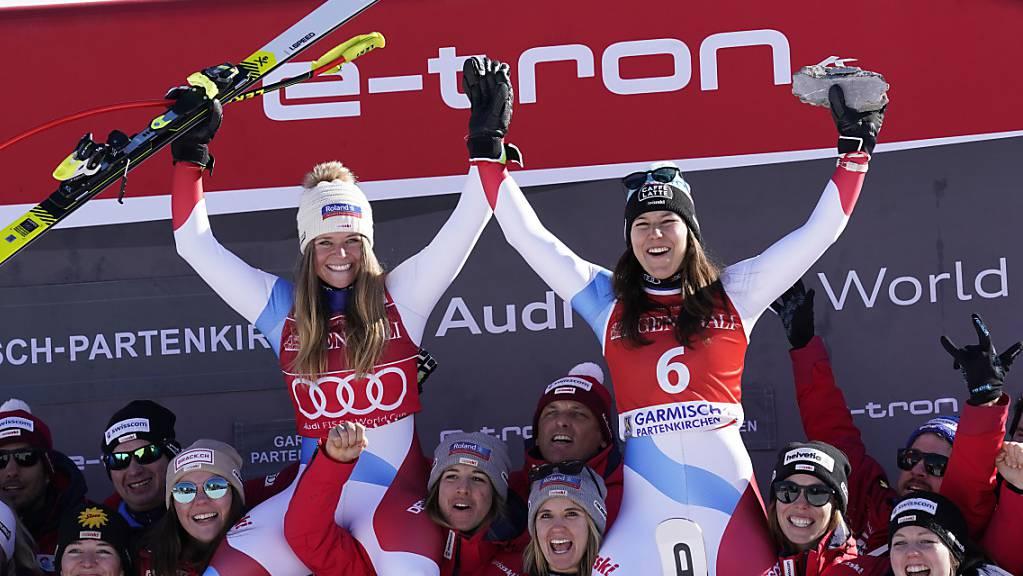 Die siegreiche Corinne Suter (links) und die drittklassierte Wendy Holdener jubeln nach dem Super-G in  Garmisch-Partenkirchen zusammen mit ihren Teamkolleginnen und den Schweizer Trainern