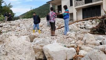 Geröll liegt vor einem überschwemmten Haus