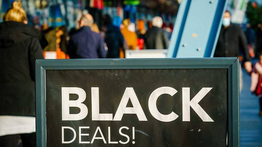 Passanten gehen vor einem Einkaufszentrum an einem Schild vorbei, das auf «Black Friday»-Angebote hinweist. Menschenmassen in Einkaufsstraßen und drohende Verstöße gegen Corona-Regeln: In den Niederlanden lehnen sich Städte gegen die Verkaufsaktion «Black Friday» auf. Foto: Marco De Swart/ANP/dpa
