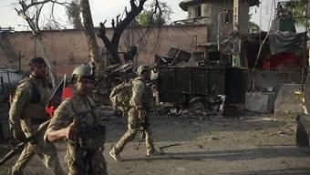 ARCHIV - Afghanische Sicherheitskräfte versammeln sich nach einem Angriff vor einem Gefängnis in Dschalalabad. Foto: Rahmat Gul/AP/dpa