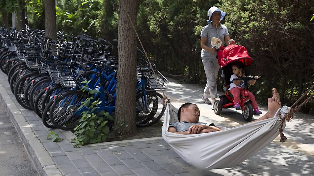 Ein Mann schläft in einer Hängematte neben Fahrrädern einer Fahrrad-Verleihfirma. Viele junge Chinesen haben das Gefühl, alles hinschmeissen zu wollen.