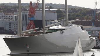 """Die Segeljacht """"Sailing Yacht A"""", wie sie am 16. September 2016 in Kiel für ein kurzes Wendemanöver aus dem Dock der Werft von Nobiskrug geschleppt wird, während ein Segelboot vorbeifährt."""