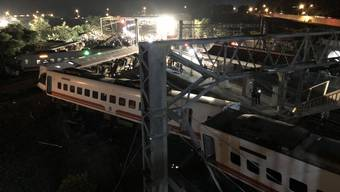 Die Wagen liegen kreuz und quer über den Geleisen: Bei einem Zugunglück im Osten Taiwans sind mindestens 18 Menschen ums Leben gekommen.