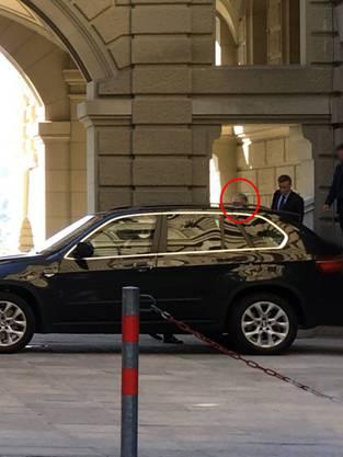 Bundesanwalt Michael Lauber (links, eingekreist, fast ganz verdeckt vom wartenden BMW der Personenschützer), gestern beim Abgang durch eine Hintertür im Bundeshaus. Rechts neben ihm Alexander Medved, sein Rechtskonsulent. Ganz rechts ein Personenschützer.