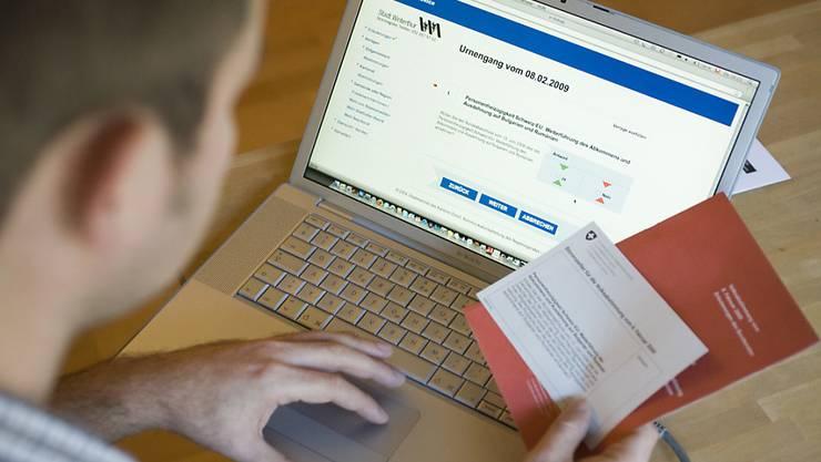 Ein Mann studiert am Laptop die Unterlagen für eine Abstimmung per e-Voting (Archivbild)
