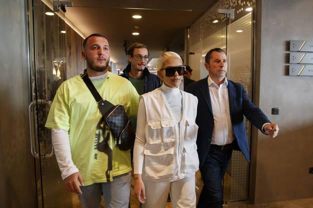 Loredana Zefi kommt mit Ehemann Mozzik (links, gelbes Shirt) und ihren Anwälten ins Hotel Emerald in Pristina.