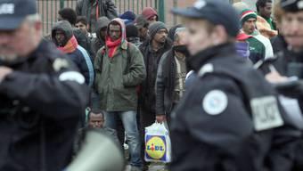 Polizisten in einem Flüchtlingslager in Calais (Archiv)