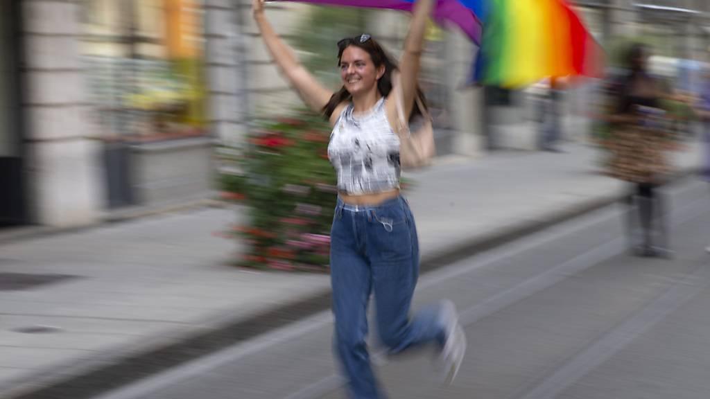 Teilnehmerin mit einer Regenbogen-Fahne an der Pride-Parade in der Genfer Innenstadt.