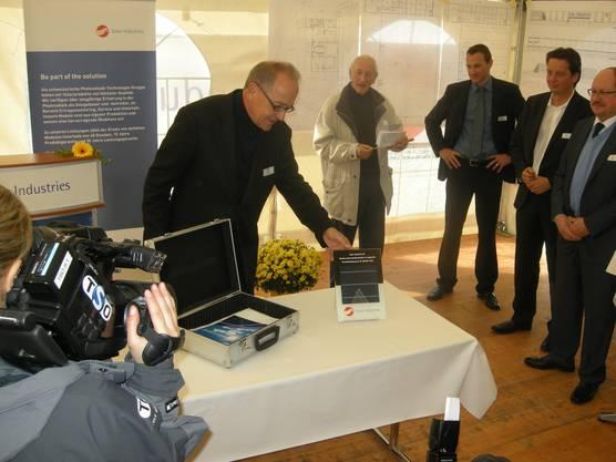 Verwaltungsrats-Präsident Rolf Wägli füllt den Koffer, der den Grundstein symbolisiert