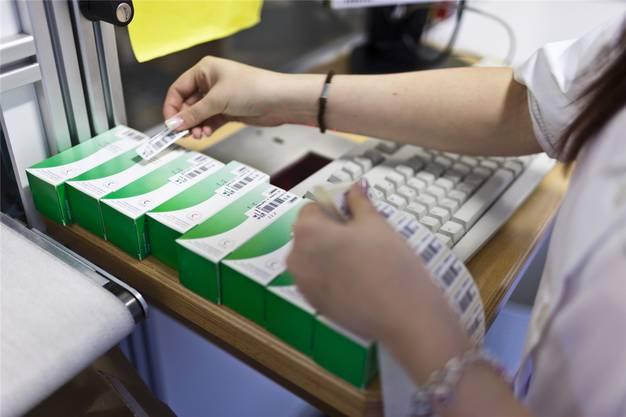 In einer Apotheke setzt eine Mitarbeiterin Strichcodes auf Medikamentenpackungen. Bild: Gaetan Bally, Baden, 13. Juli 2012