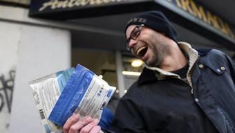Ein Mann zeigt zwei legal in einer Apotheke in Uruguays Hauptstadt Montevideo gekaufte Packungen Marihuana.