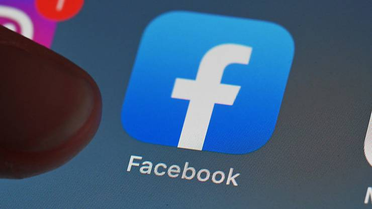 ARCHIV - ILLUSTRATION - Eine Person zeigt auf einem Tablet auf die Facebook App. Foto: Uli Deck/dpa