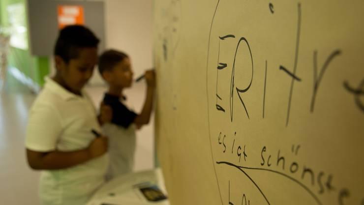 Multikulti - Kinder schreiben ihre Herkunft auf eine Tafel. (Symbolbild)