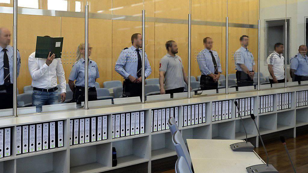 Die drei Angeklagten, jeweils flankiert von zwei Sicherheitsleuten, im Oberlandesgericht Düsseldorf