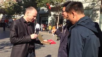 Rolf Meyer, Leiter des KMU-Centers, offeriert Suteria-Schokolade in der Einkaufsmeile von Harbin.