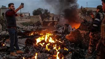 Ein Selfie mit den Trümmern des Kampfflugzeugs: Rebellen posieren am Samstagabend in der Provinz Idlib. Keystone/EPA