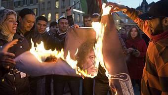 Ein Bild von Gaddafi wird in Bern verbrannt