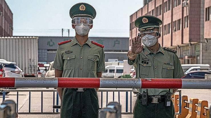 Maskierte Polizisten bewachen den Xinfadi-Markt in Peking.