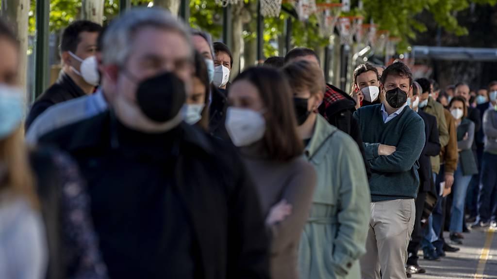 Menschen stehen Schlange, um ihre Stimme während der Regionalwahlen in Madrid abzugeben. Foto: Manu Fernandez/AP/dpa