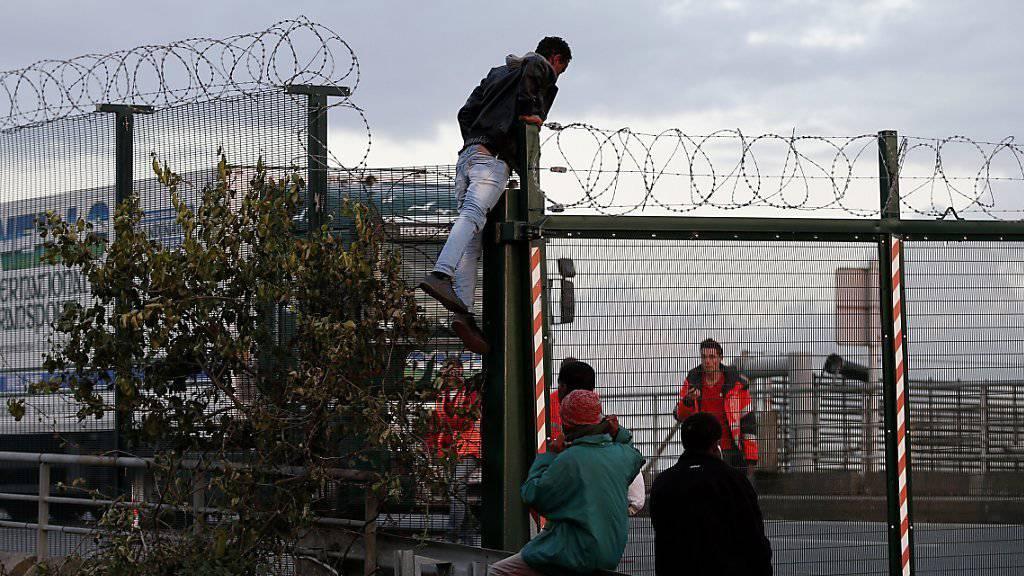 Hunderte Migranten versuchen jede Nacht in Calais, auf einen Güterzug Richtung Grossbritannien zu gelangen. Daran gehindert werden sie durch Abschrankungen und von einem Grossaufgebot an Polizisten.