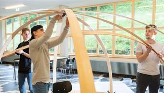 Lernende der BBB formen aus Holzlatten Kunstobjekte.