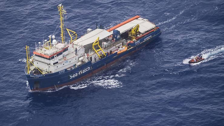 Ein Boot holt zwei Flüchtlinge vom Rettungsschiff Sea Watch 3, das vor Lampedusa blockiert ist.