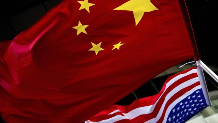 ARCHIV - Die US-amerikanische (unten) und chinesische Nationalflaggen wehen vor einem Hotel. (zu dpa «China: USA fordern Schließung des chinesischen Konsulats in Houston») Foto: Andy Wong/AP/dpa