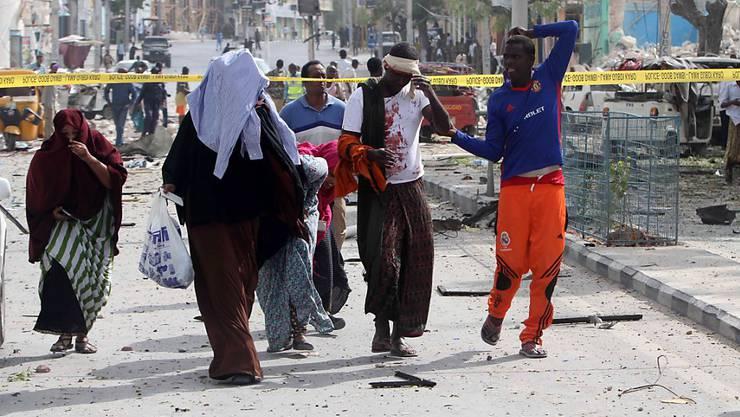Verletzte verlassen das Gelände vor dem Hotel, wo nach dem Angriff überall Trümmer liegen.