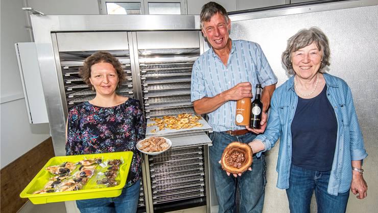 Andrea Buser (links) und Dora Meier (rechts) mit ihren Produkten sowie Felix Schweizer mit Kirsch- und Zwetschgensaft vor der neuen Dörranlage.Nicole Nars-Zimmer