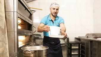 Kerim Demirbas stellt Baklava in seiner Backstube selbst her. Während der Teig im Ofen bäckt, kocht der Sirup in der Schüssel.