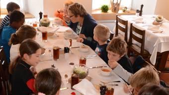 Ellenbogen nicht aufstützen und den Suppenlöffel richtig halten: Beim Essen im «Bären» zeigen die Kinder, was sie gelernt haben.lbr