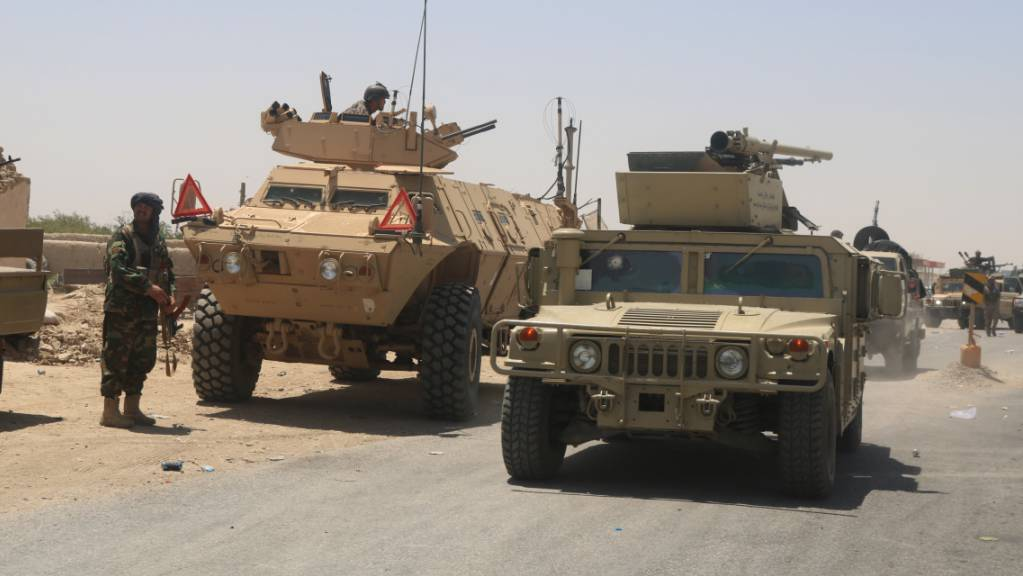 Ein afghanischer Sicherheitsbeamter (l) steht mit einer Schusswaffe auf einer Strasse neben Militärfahrzeugen. Nach dem Abzug der internationalen Truppen hat die militant-islamistischen Taliban ihre Offensiven im Land verstärkt und mehrere Bezirke übernommen.